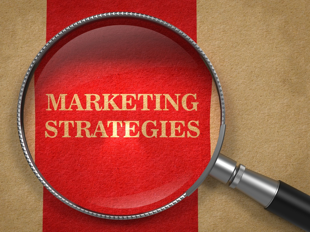 Marketing Strategies. Magnifying Glass on Old Paper with Red Vertical Line..jpeg
