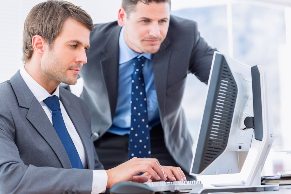 Smartly dressed young businessmen using computer at office desk.jpeg